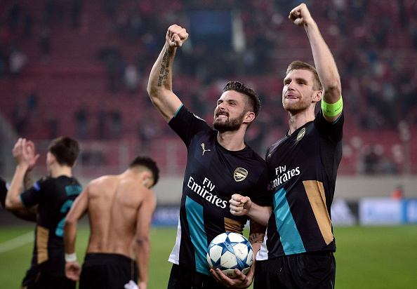 Arsenal's French forward Olivier Giroud (L)and Arsenal's German defender Per Mertesacker celebrate after the UEFA Champions League Group F football match between Olympiacos and Arsenal at the Georgios Karaiskakis Stadium in Piraeus near Athens on December 9, 2015. Arsenal won the match 0-3. (Photo by LOUISA GOULIAMAKI/AFP/Getty Images)