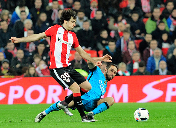 Athletic Bilbao's defende Inigo Lekue (L) vies with Barcelona's Turkish midfielder Arda Turan during the Spanish Copa del Rey (King's Cup) football match Athletic Club de Bilbao vs FC Barcelona at the San Mames stadium in Bilbao on January 20, 2016. (Photo by ANDER GILLENEA/AFP/Getty Images)