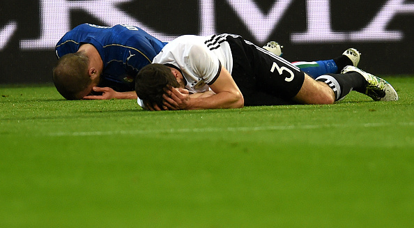 Germany's Hector (R) and Italy's Insigne (L) are shown laying on the ground after a clash. (Photo by PATRIK STOLLARZ/AFP/Getty Images)